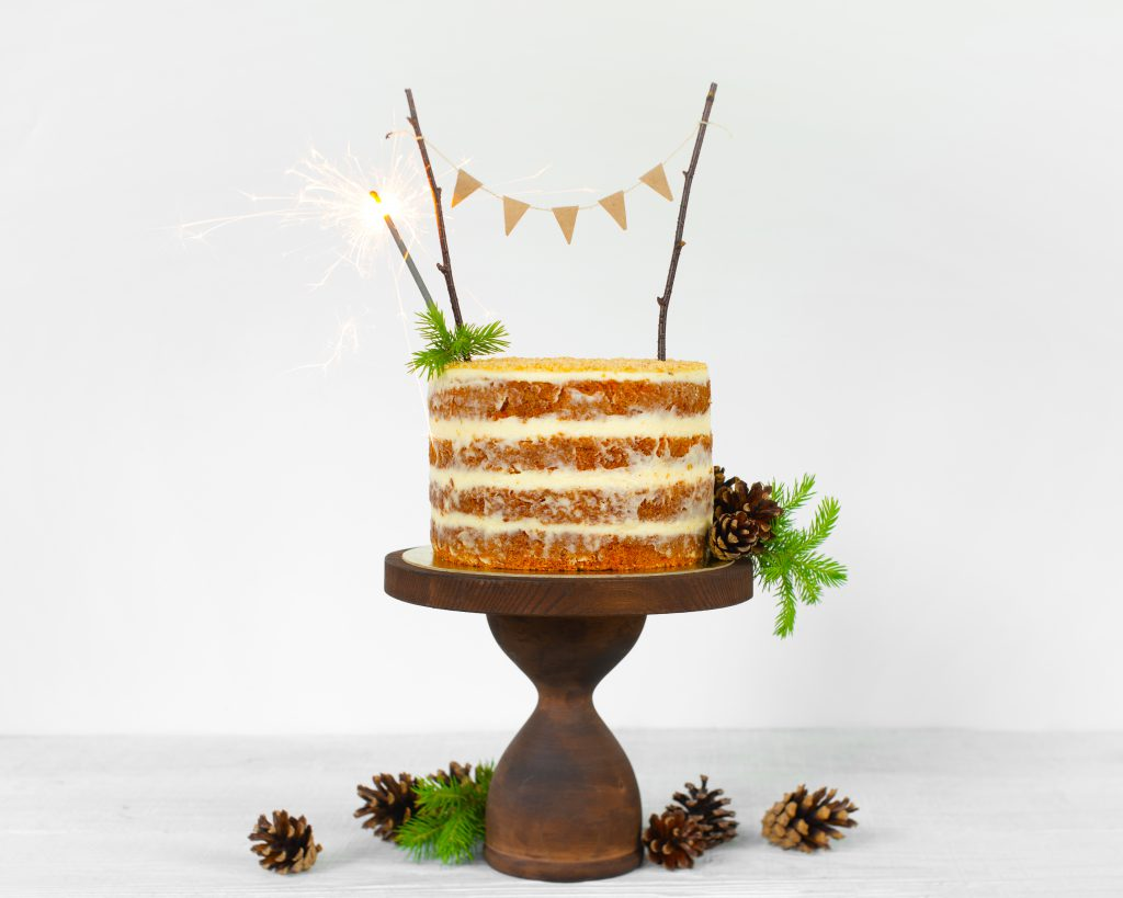 Fresh holiday naked carrot cake with cream decorated with pine c